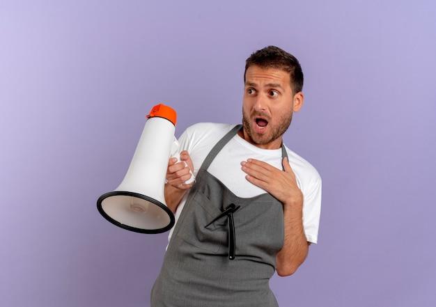 Kapper man in schort met megafoon opzij kijken met angst expressie staande over paarse muur