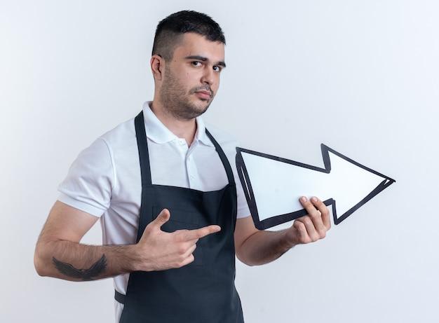 Kapper man in schort met pijl die met wijsvinger wijst en ziet er zelfverzekerd uit terwijl hij over wit staat