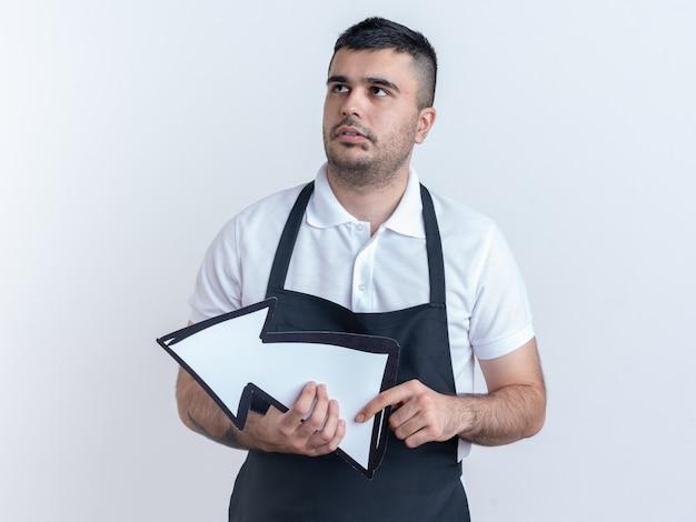 Kapper man in schort met pijl omhoog kijkend verbaasd staande over witte achtergrond