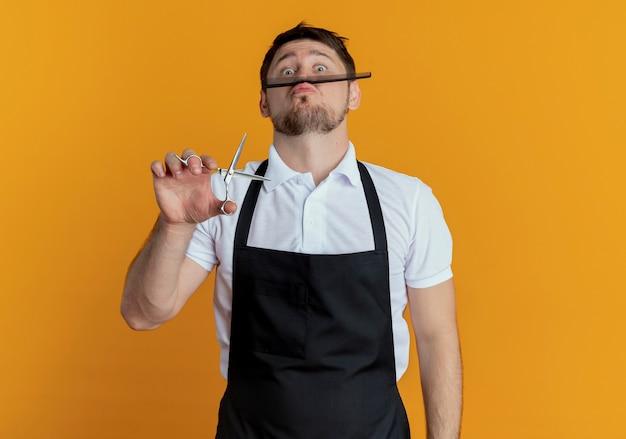 Kapper man in schort met schaar en kam plezier staande over oranje muur