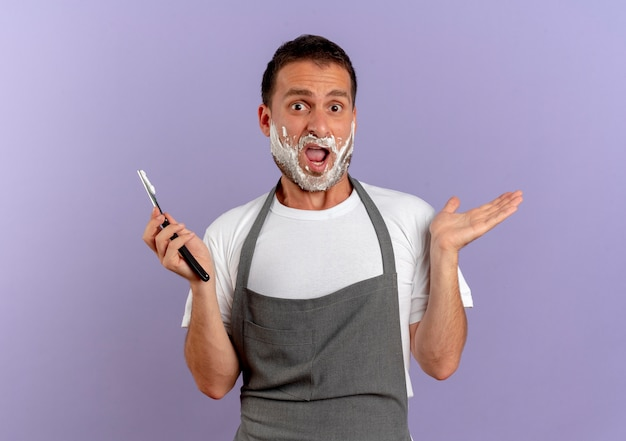 Kapper man in schort met scheerschuim op zijn gezicht met scheermes naar voren kijkend verward schouderophalend staande over paarse muur