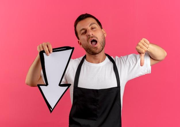 Kapper man in schort met witte pijl naar voren kijkend ontevreden met duimen naar beneden staande over roze muur