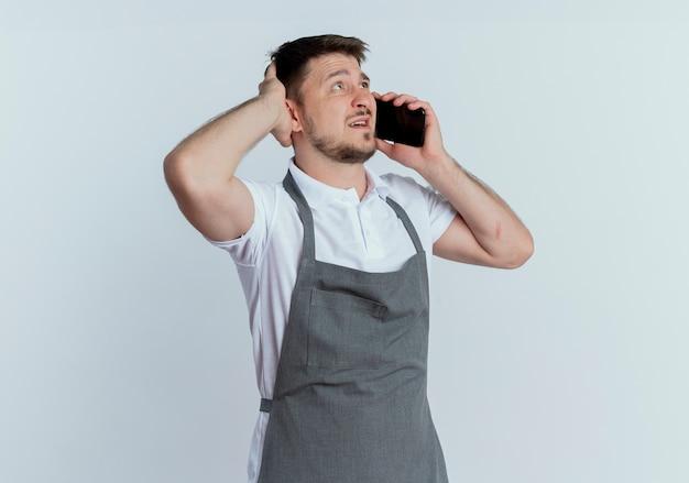 Kapper man in schort op zoek verward tijdens het praten op mobiele telefoon staande op witte achtergrond
