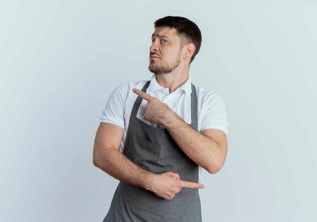 Kapper man in schort opzij kijken met ernstig gezicht wijzend met wijsvingers naar verschillende richtingen staande op witte achtergrond