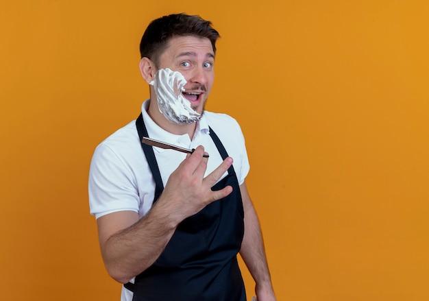 Kapper man in schort scheerschuim zetten zijn baard glimlachend weergegeven: scheermes staande over oranje muur