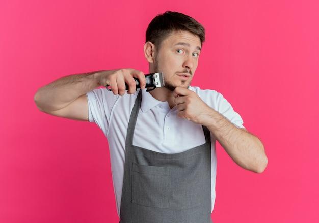 Kapper man in schort trimmen zijn baard staande over roze muur