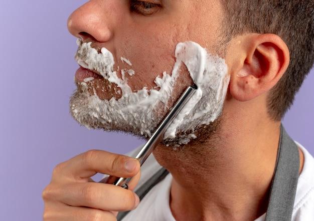 Kapper man met scheerschuim op zijn gezicht zichzelf scheren met scheermes over paarse muur