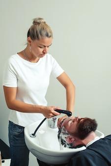 Kapper man wast het hoofd van de klant in de kapperszaak. haarstylist kapper wassen klant haar - brutale man ontspannen in kappers schoonheidssalon. kapper wassen hoofd klant. man bij kapperszaak.