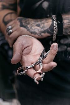 Kapper mans handen met een schaar
