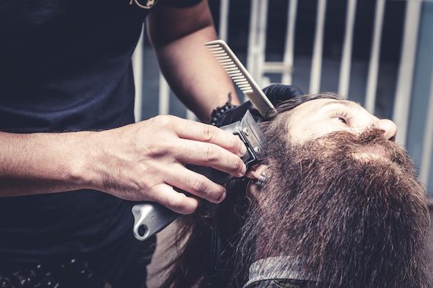 Kapper met behulp van scheerapparaat om baard van een man te snijden.