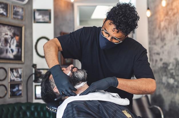 Kapper met een beschermingsmasker een klant scheren met een scheermes