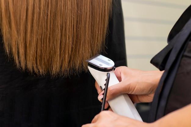 Kapper met een haarmachine die gespleten haarpunten afsnijdt
