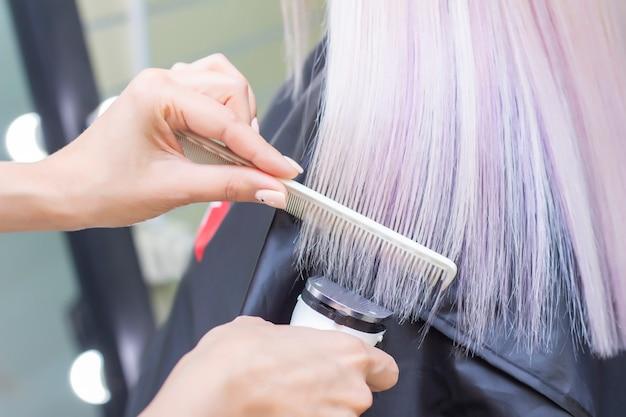 Kapper met een haarmachine. gespleten haarpunten afknippen met een tondeuse. detailopname.