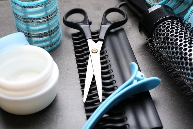 Kapper met gereedschap en cosmetica op grijs