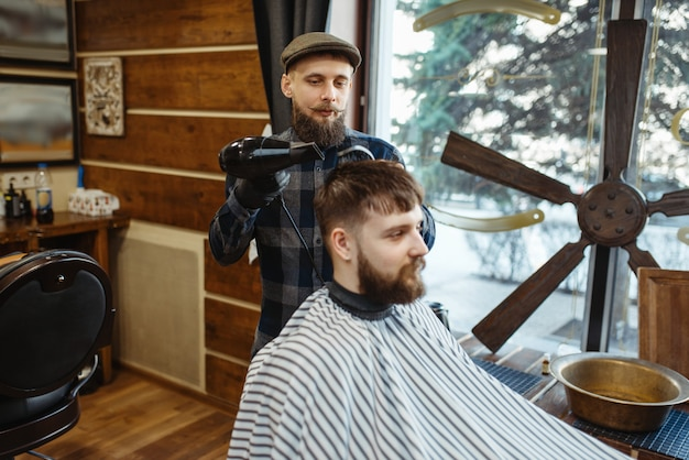 Kapper met kam en haardroger maakt een kapsel voor een klant. professionele kapperszaak is een trendy beroep