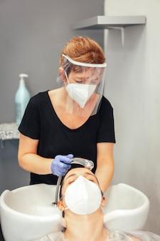 Kapper met masker en handschoenen die het haar van de cliënt met water wassen. heropening met veiligheidsmaatregelen van kappers in de covid-19 pandemie