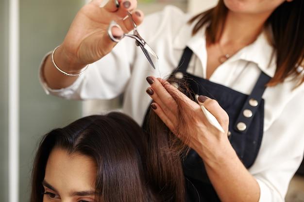 Kapper met schaar knipt vrouw haar, kapsalon. stylist en klant in kapsalon. schoonheidsbedrijf, professionele service