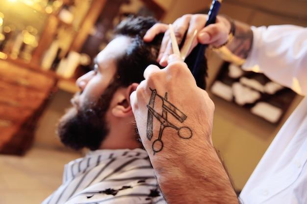 Kapper of kapper doet een kapsel aan de klant op de achtergrond van moderne kapperszaak