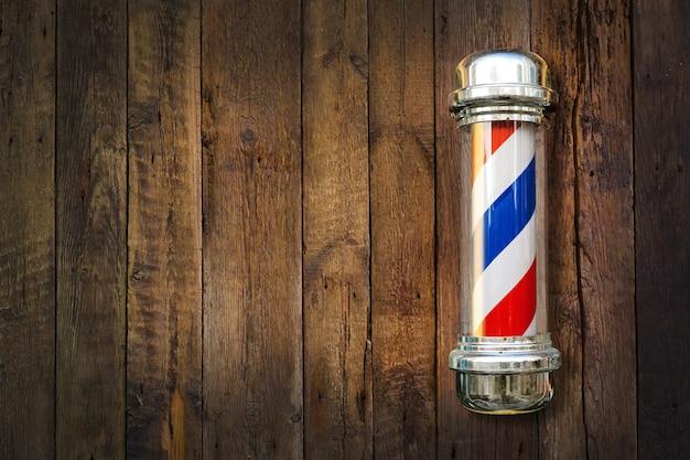 Kapper paal. barbershop paal op een houten achtergrond met kopie ruimte.