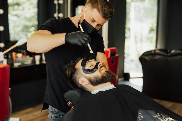 Kapper past een zwart houtskoolmasker toe op het gezicht van de man om de poriënhuid te reinigen en acne uit de neus te verwijderen in de kapper