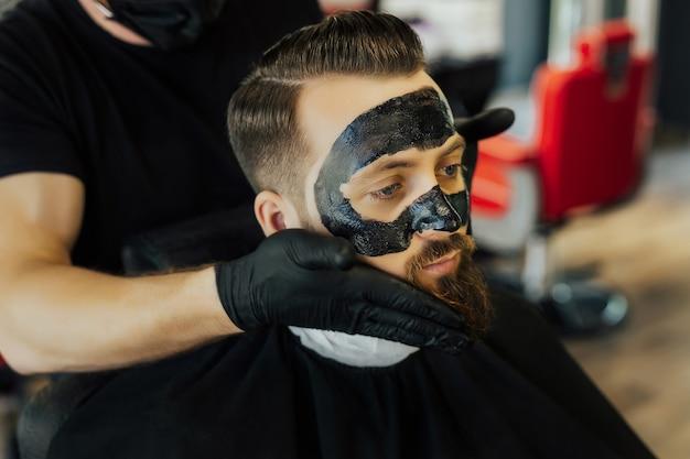 Kapper past een zwart houtskoolmasker toe op het gezicht van de man om de poriënhuid te reinigen en acne uit de neus te verwijderen in de kapperszaak