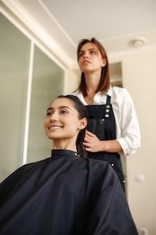 Kapper past mousse toe op het haar van de vrouw, vooraanzicht, kapsalon. stylist en klant in kapsalon. schoonheidsbedrijf, professionele service