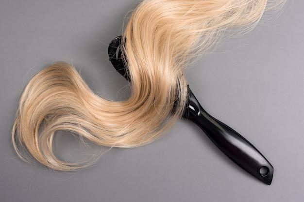 Kapper professionele haarborstel en blonde haarkrul geïsoleerd op een grijze achtergrond