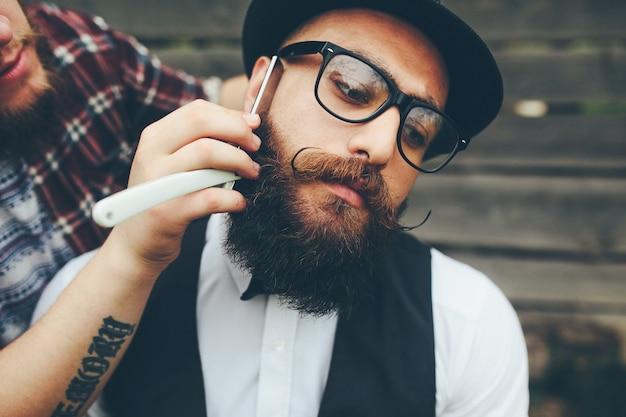 Kapper scheert een bebaarde man in vintage sfeer