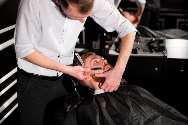 Kapper scheert mannelijke baard met het mes. knappe bebaarde man wordt geschoren door kapper in de kapperszaak