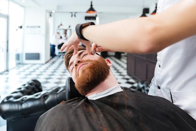 Kapper scheren man met open scheermes in kapperszaak