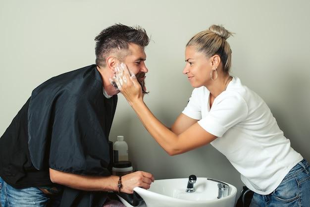 Kapper schildert baard en snor in zwarte kleur van hipster man in kapperszaak. haarstylist kapper wassen klant baard - brutale man ontspannen in kappers schoonheidssalon.