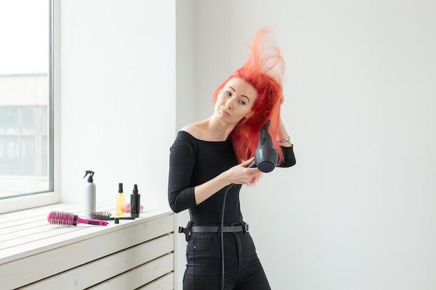 Kapper, schoonheidssalon en mensenconcept - jonge vrouwenkapper met haardroger op witte muur.