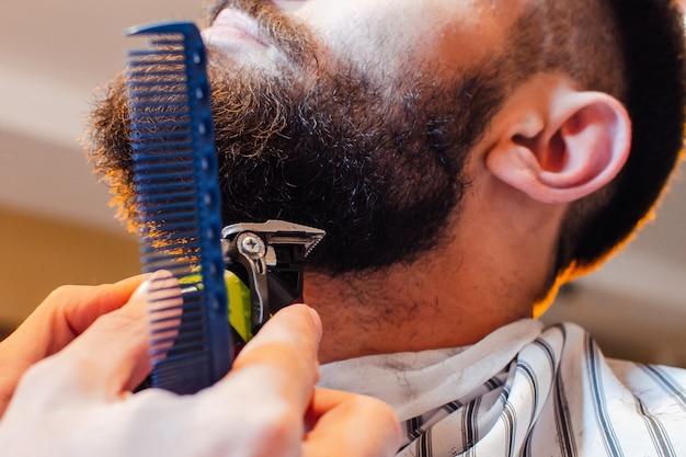Kapper snijdt een baard met een trimmer tot een jonge knappe kerel met een snor