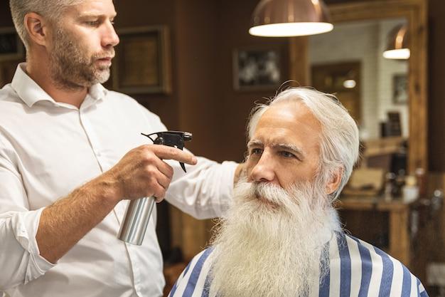 Kapper stijlvolle kapsel maken voor een knappe oude man in de kapperszaak