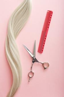Kapper tools schaar, kammen en streng van blond haar op roze kleur achtergrond schoonheidssalon service