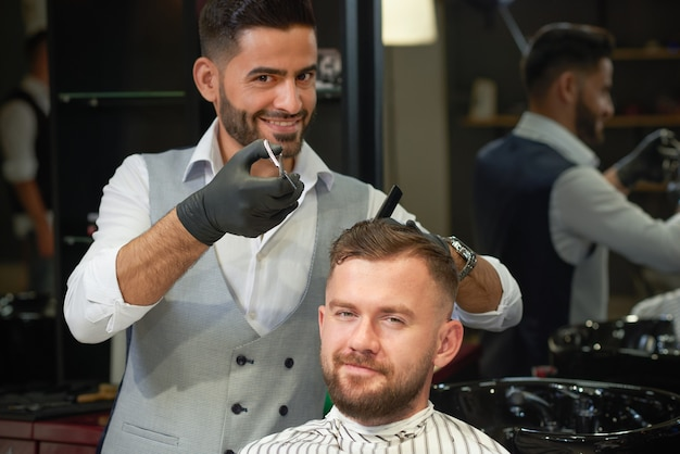Kapper trendy kapsel doen aan jonge man in kapperszaak
