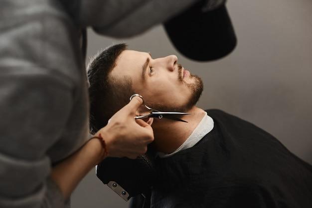Kapper trimt stijlvolle baard van de knappe brute jongeman met modieus kapsel die in de fauteuil bij een kapperszaak zit