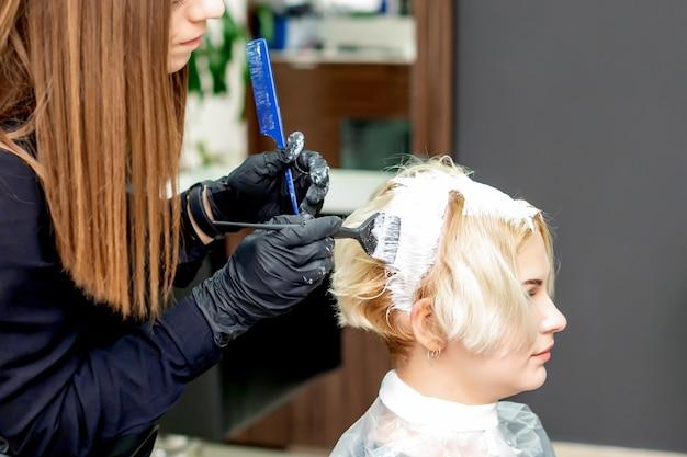 Kapper verft haar van vrouw in witte kleurstof in schoonheidssalon.