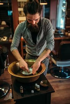 Kapper voorbereiding van scheerschuim in een koperen kom op barbershop.