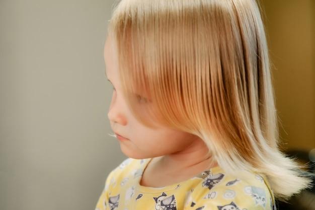 Kapper vrouw maakt modieus mooi kapsel voor schattig klein blond meisje kind in moderne kapperszaak, kapsalon. kapper maakt kapsel voor jonge baby in kapperszaak. concept kapsel en schoonheid