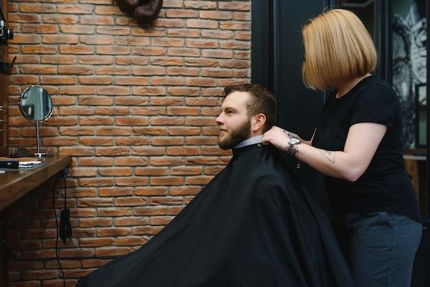 Kapper vrouw man haar knippen bij de barbershop.