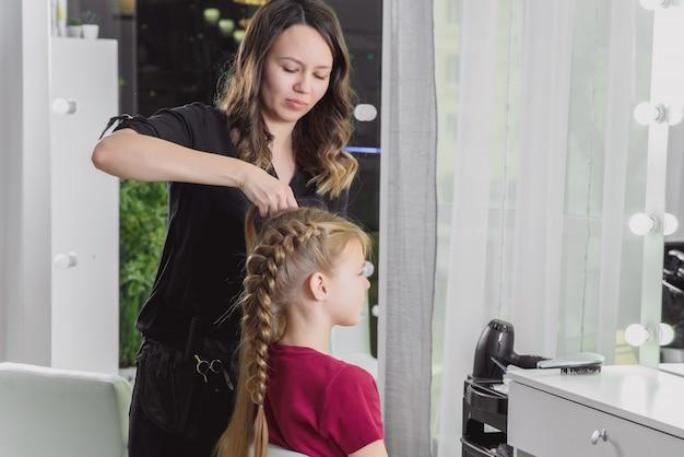 Kapper weeft een vlecht aan een preteen blond meisje in een schoonheidssalon en kapsalon