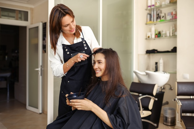 Kapper werkt met het haar van de vrouwelijke klant bij de spiegel in de kapsalon. stylist en klant in kapsalon. schoonheidsbedrijf, professionele service