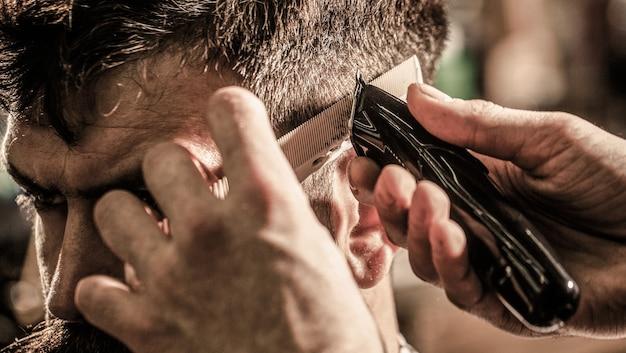Kapper werkt met tondeuse. hipstercliënt die kapsel krijgt. handen van kapper met tondeuse, close-up.