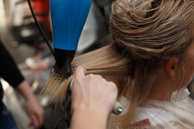 Kappers handen drogen blond haar met föhn en ronde borstel