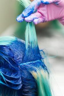 Kappers met hand in beschermende handschoen heffen schok van modern blauw haar van cliënt op tijdens haarverfproces in professionele schoonheidssalon.