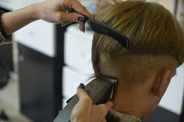Kappersdiensten. een man knipt haar bij een kapper-stylist in een herenkapper. schaar kam, clipper close-up. kapper op het werk. close-up knippen van haar.