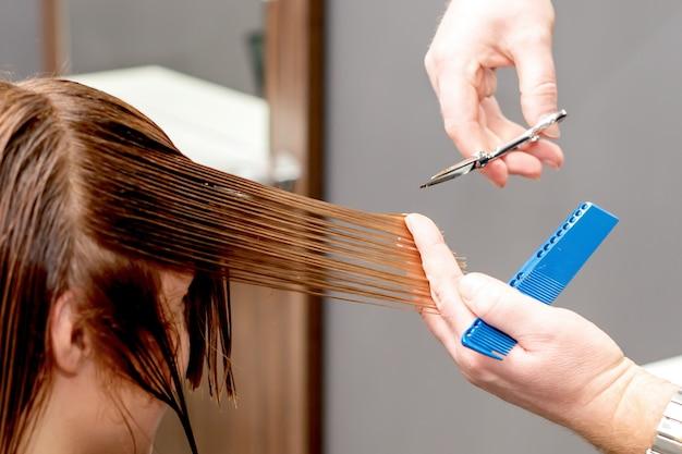 Kappershanden die haar van vrouw knippen.