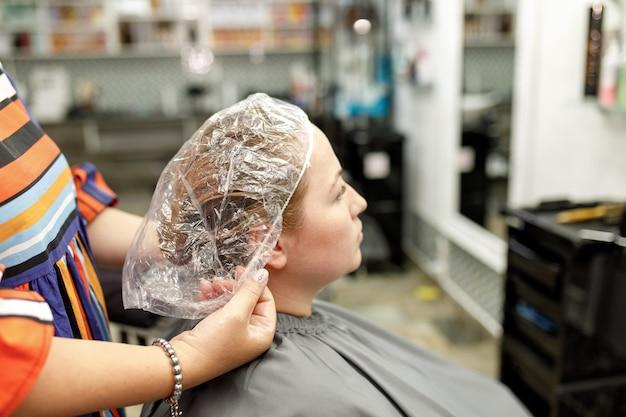 Kappershanden zetten een transparante dop op het hoofd van de klant tijdens cosmetische haarbehandelingen