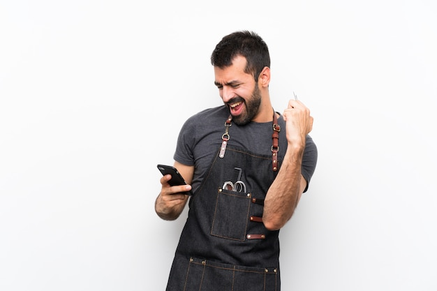 Kappersmens in een schort met telefoon in overwinningspositie